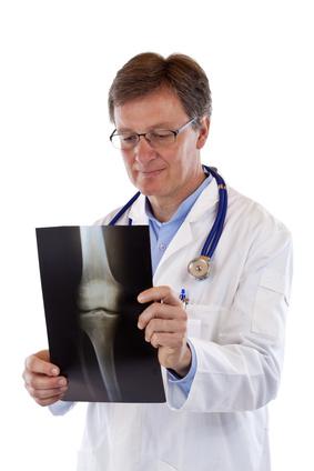 Arzt betrachtet Röntgenbild eines Kniegelenks